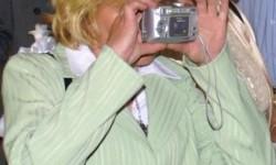 Une blonde qui utilise un appareil photo